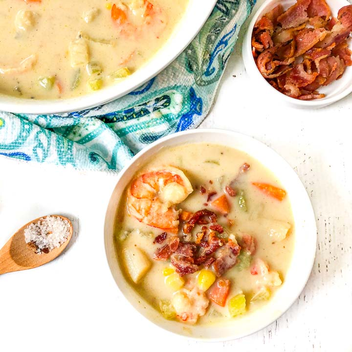 aerial view of white bowl with creamy keto seafood chowder with a bowl of bacon crumbles and a wooden spoon with salt