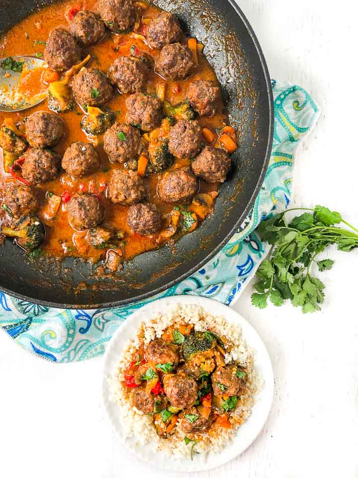 aerial view of a skillet and white plate with curry meatballs and a bunch of fresh cilantro