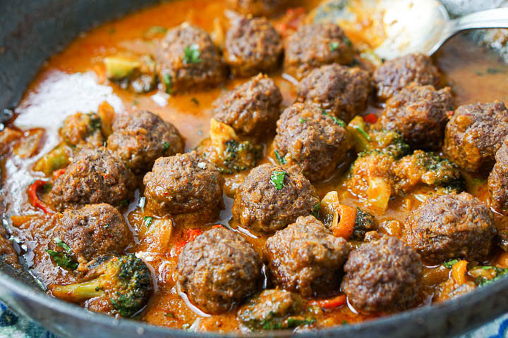 closeup of meatballs in a spicy coconut curry sauce and vegetables with a spoon in the background