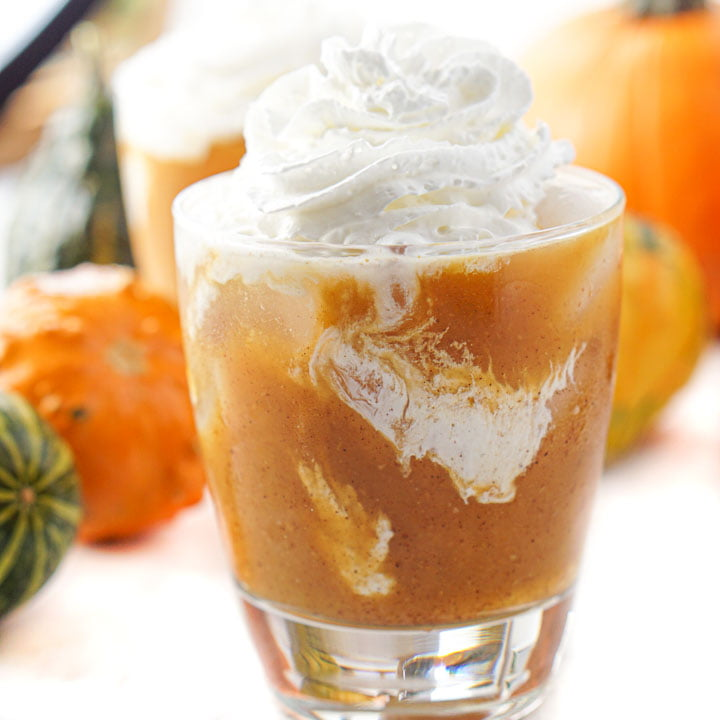 closeup of a glass of keto pumpkin pie cocktail with whipped cream on top and pumpkins and gourds in the background