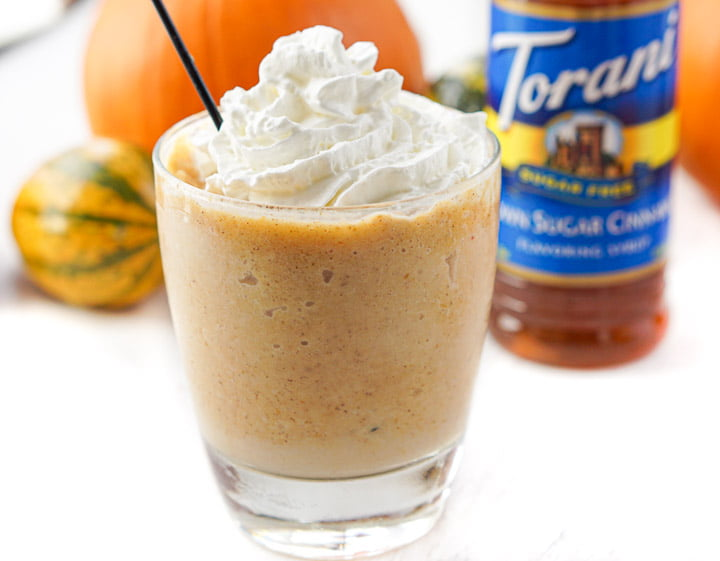 frozen keto pumpkin pie slushy with black straw and whipped cream with bottle in background
