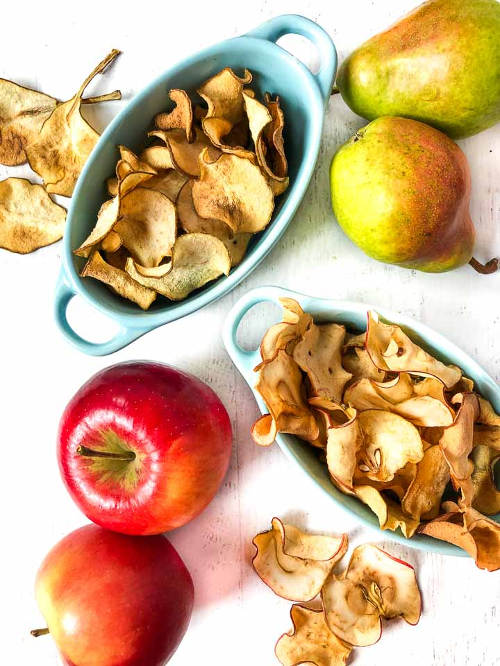 two blue dishes - one with dried pear chips and the other with dried apple chips and fresh red apples and green pears