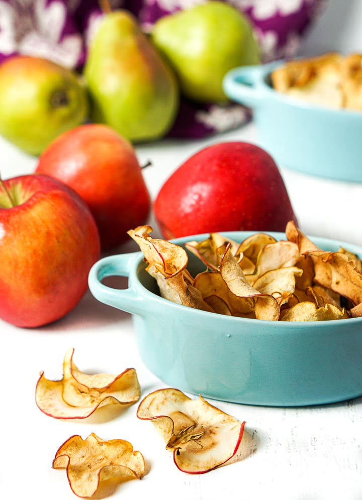 blue dish with crispy apple chips and apple and pears in the background