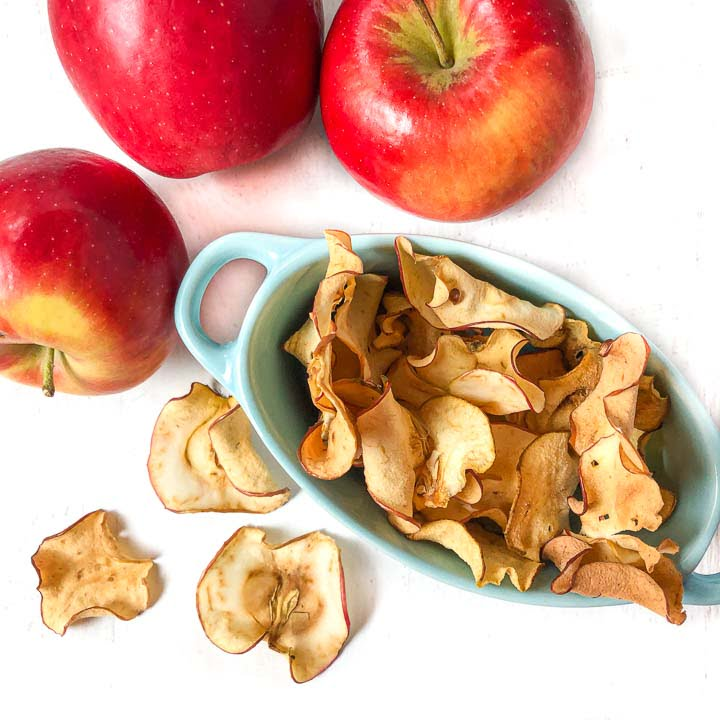 blue dish with healthy apple chips made in the air fryer and a few bright red apples