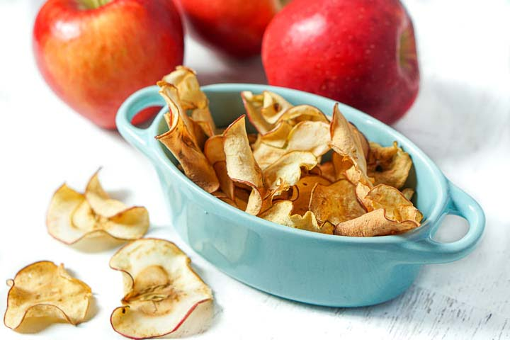 blue dish with apple chips  and a few bright red apples and scatter thin apple chips