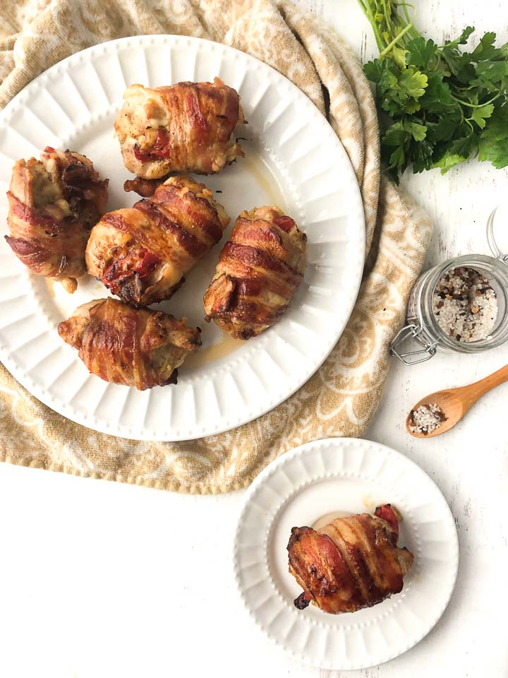 white plates with the low carb chicken thighs wrapped in bacon and a bunch of fresh parsley