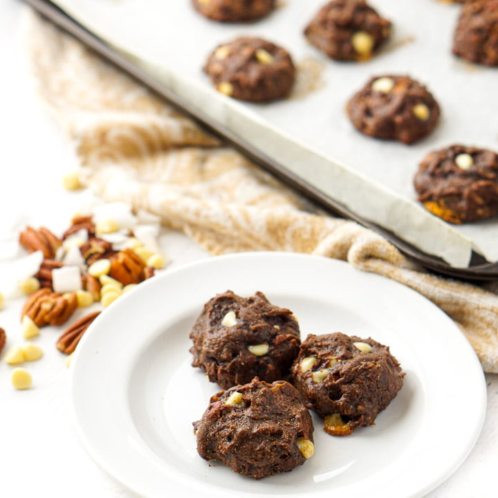 white plate with keto chocolate almond butter cookies with scattered pecans and white chocolate chips