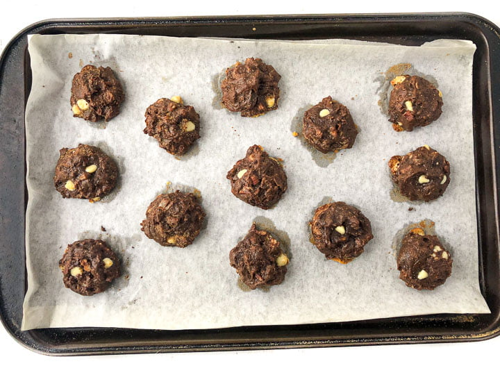cookie sheet covered with parchment paper and baked sugar free chocolate cookies