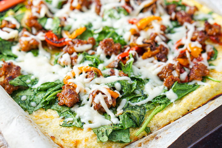 closeup of gluten free cauliflower crust with fresh spinach, Italian sausage and peppers