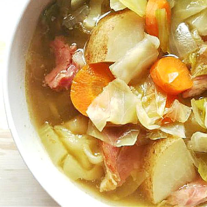 closeup of a bowl of ham and cabbage soup in a white bowl