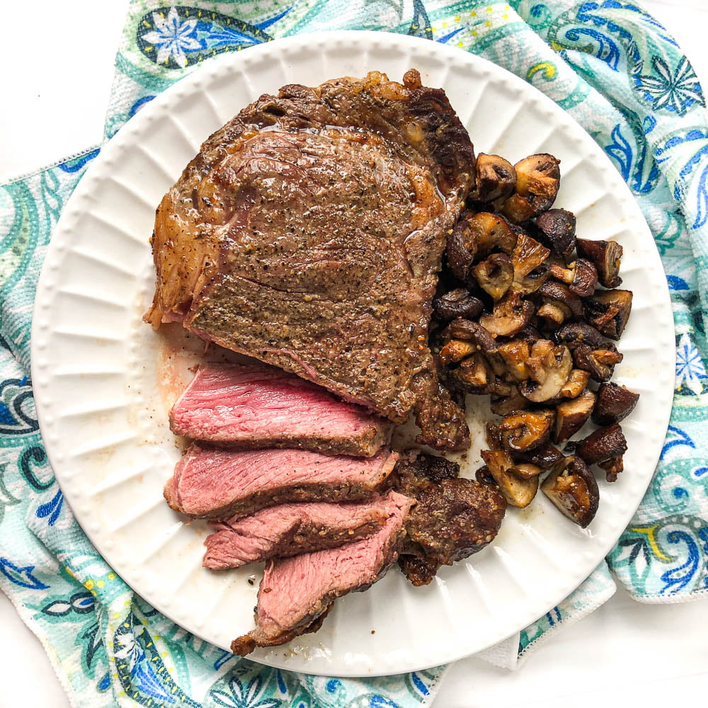 large ribeye steak sliced with garlic mushrooms on white plate