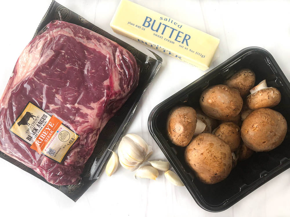 steak with garlic butter ingredients: raw ribeye steak, garlic cloves, butter, and baby portobello mushrooms
