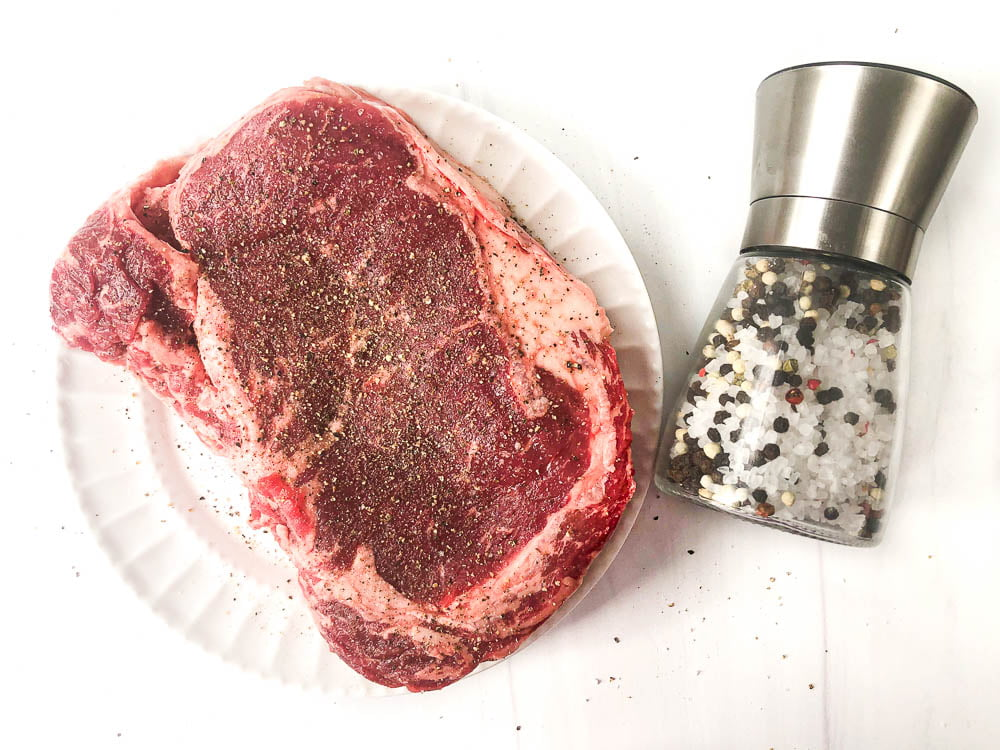 raw steak on white plate with lots of salt and pepper and a salt and pepper shaker next to it