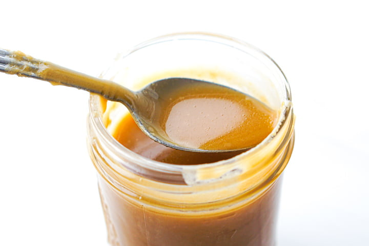 a closeup of a spoon full of butterscotch syrup