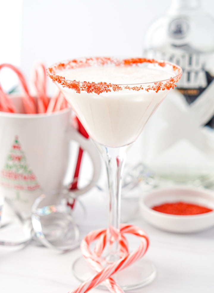 glass with peppermint martini with candy canes around the stem