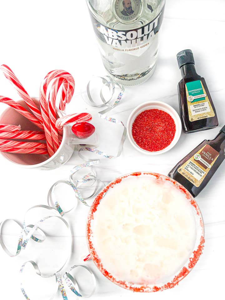 aerial view of peppermint and vanilla extract, a mug of candy canes, vanilla vodka, red sugar, a silver ribbon and creamy martini