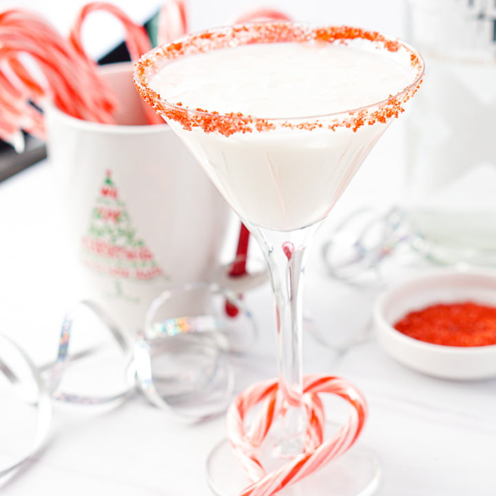 martini glass with keto candy cane drink with a mug full of candy canes in the background