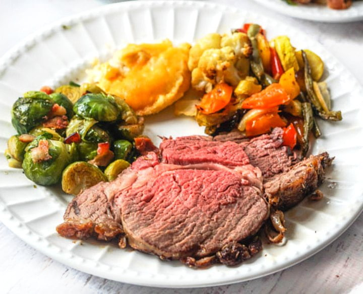 white plate with keto Christmas dinner with roast beef, and low carb sides