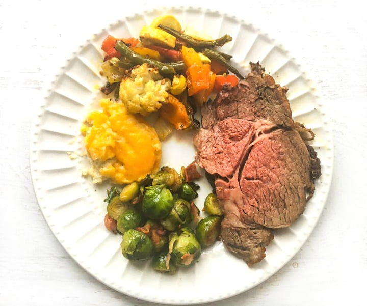 white plate with a slice of prime rib and low carb side dishes