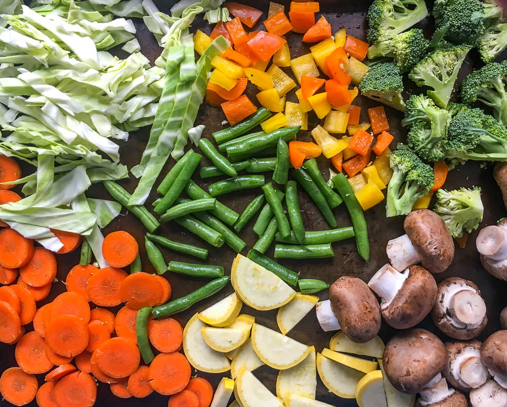 fresh chopped vegetables for soup - cabbage, peppers, broccoli, green beans, carrots, yellow zucchini and mushrooms
