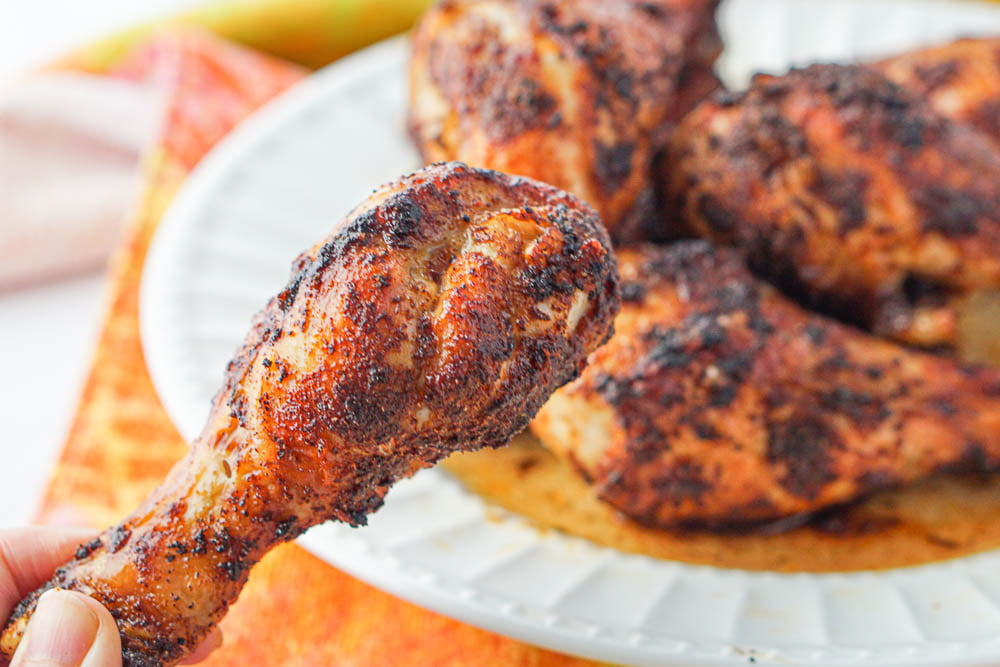fingers holding a crispy spice rubbed chicken leg with a plateful in the background