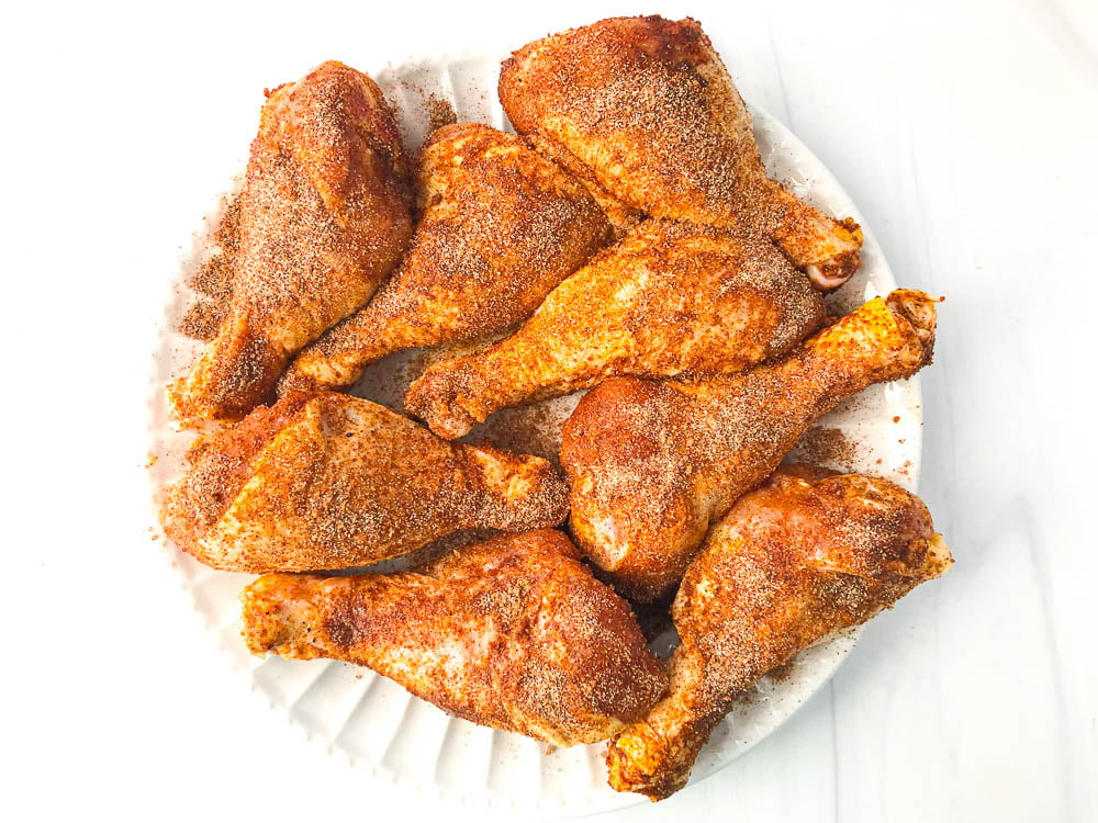 white plate with spice rubbed raw chicken legs
