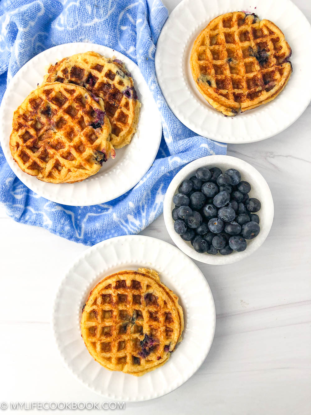 aerial view of 3 white plates with mini low carb blueberry waffles and a bowl of fresh blueberries
