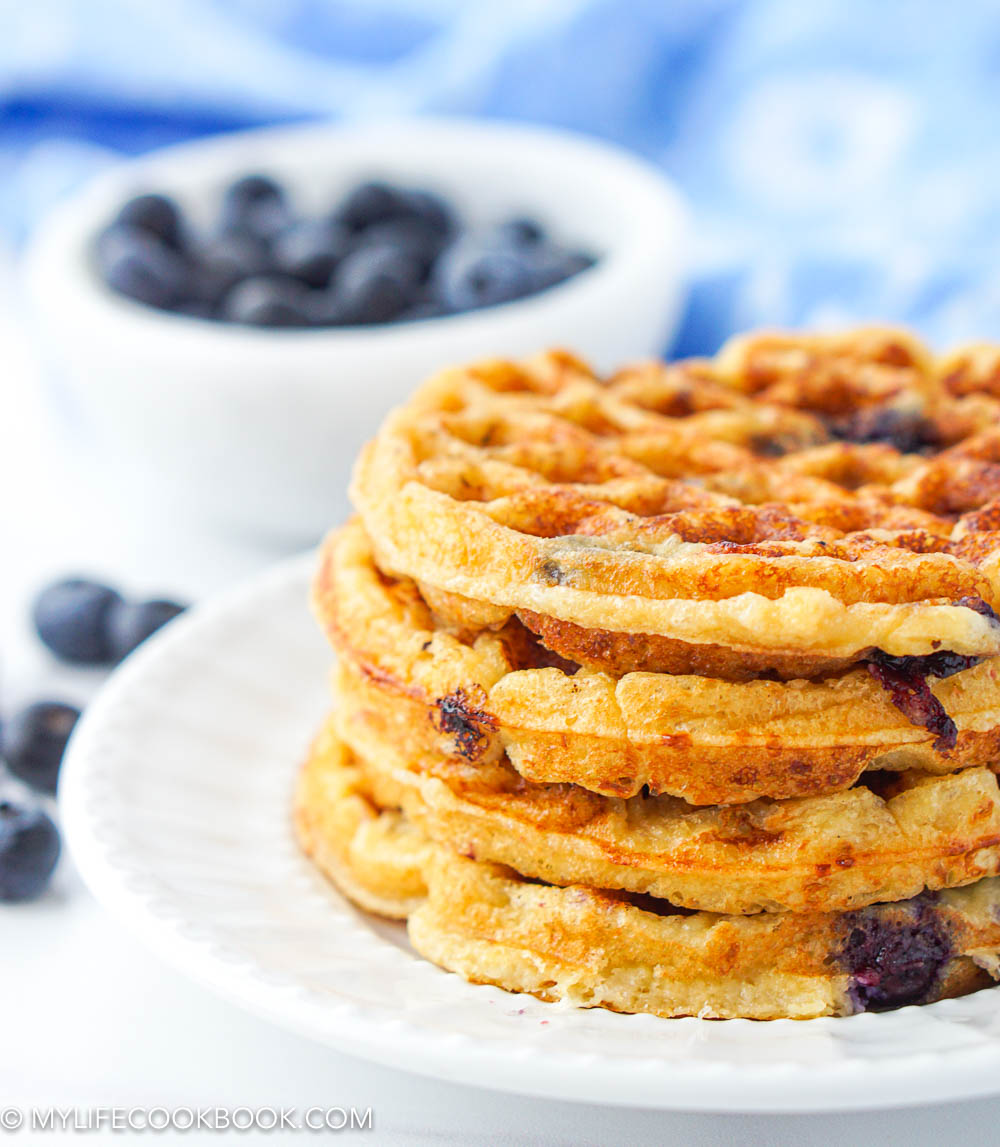 closeup of a stack of sugar free and gluten free waffles with blueberries in background