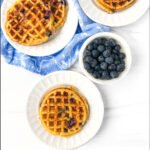 aerial view of white plates with keto blueberry waffles and fresh blueberries and text