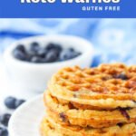 closeup of a white plate with a stack of keto blueberry waffles and fresh blueberries in background and text