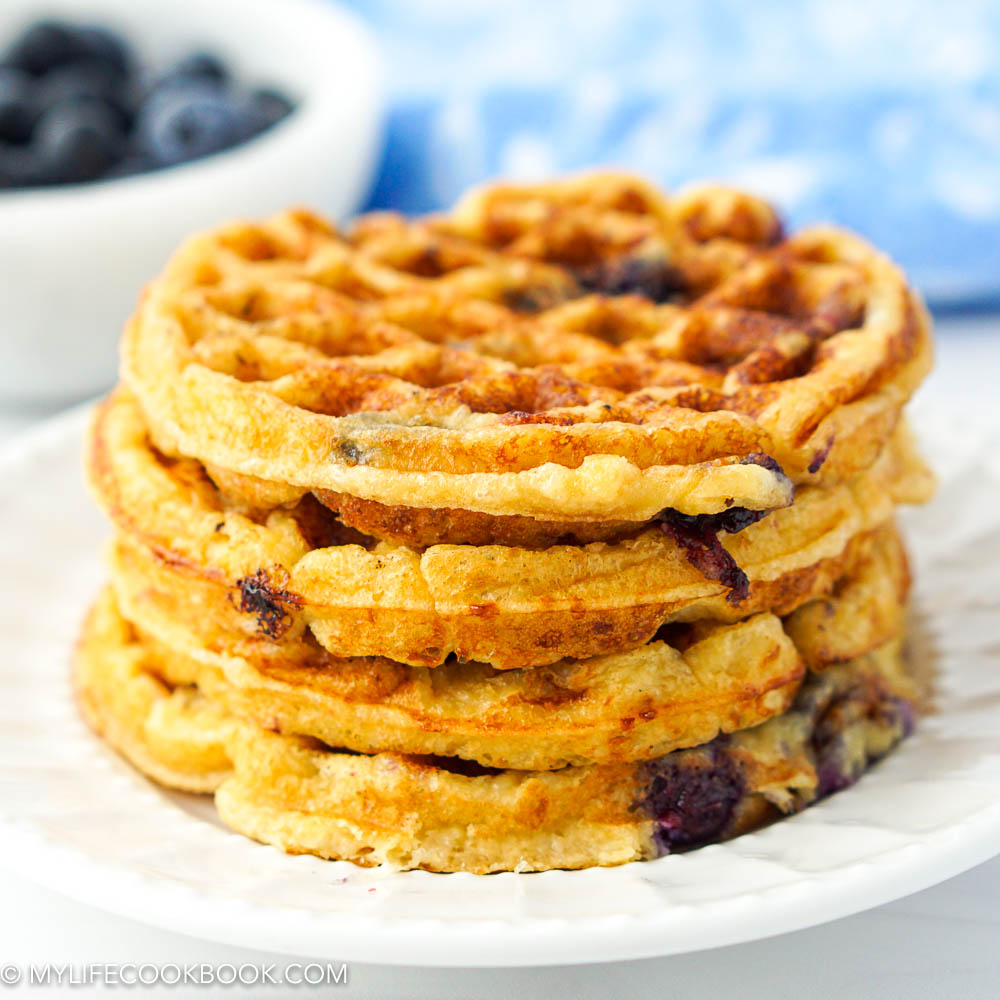 closeup of a stack of keto blueberry chaffles on a white plate