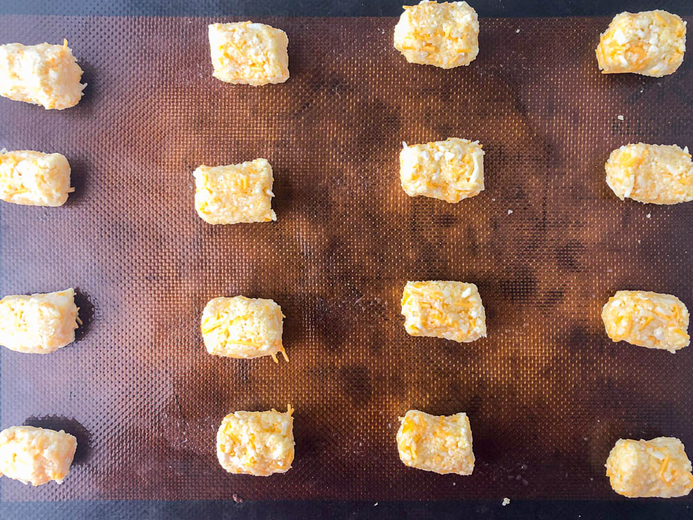 closeup of cookie sheet with raw cauliflower tots