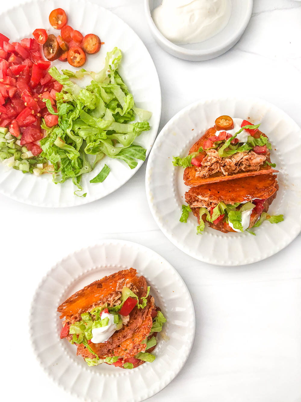 aerial view of 2 white plates with low carb mini tacos and a plate with taco toppings
