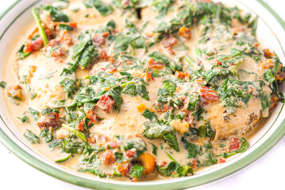closeup of the big bowl with keto chicken breasts, covered in creamy spinach and sun dried tomato sauce