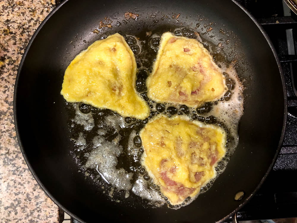 black skillet with 3 pieces of low carb tilapia Romano sizzling