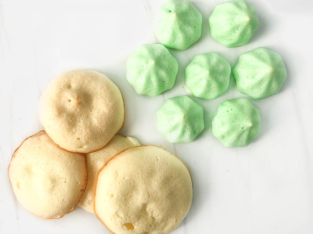 yellow flatter meringue cookies and some of the green piped meringue cookies showing the difference between using a standing mixer and hand mixer