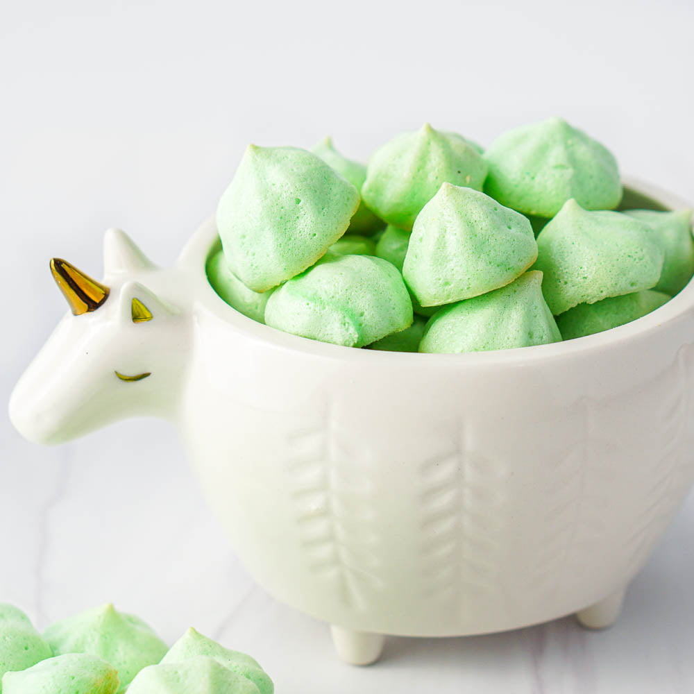 white unicorn bowl filled with green keto meringue cookies