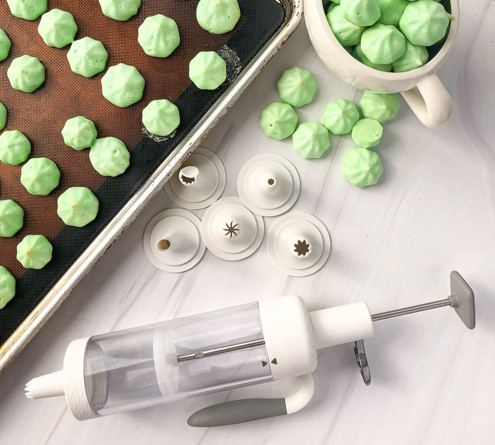 cookie sheet and unicorn mug with green meringue cookies and a cookie gun with icing tips