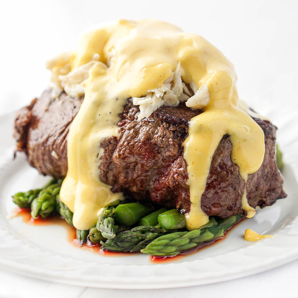 closeup of a piece of filet topped with crabmeat and keto hollandaise sauce with asparagus underneath