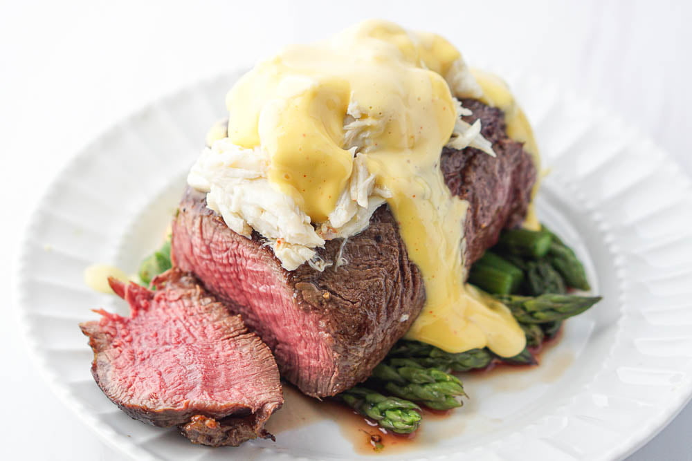 closeup of a keto steak Oscar dish on a white plate - the filet is sliced and topped with crab and creamy hollandaise sauce