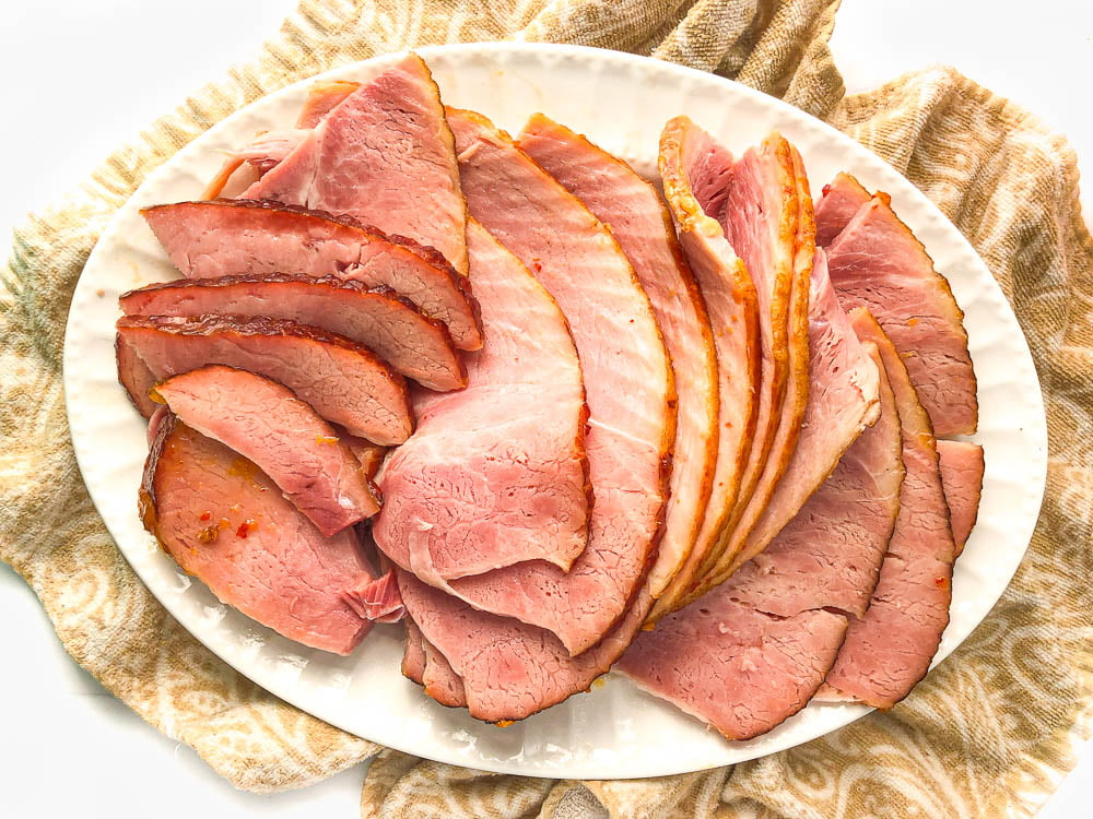 aerial view of just a white platter with the sliced up apricot glazed ham