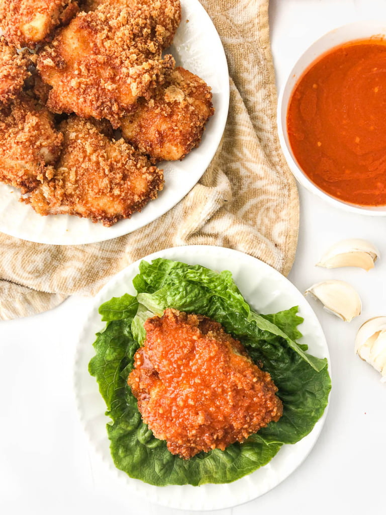 aerial view of white plates with air fried chicken and keto buffalo sauce, garlic cloves and lettuce