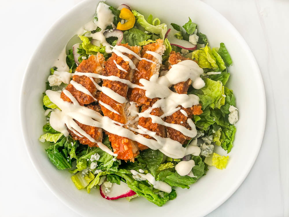 aerial view of a pretty salad with fried  chicken strips, blue cheese and ranch dressing