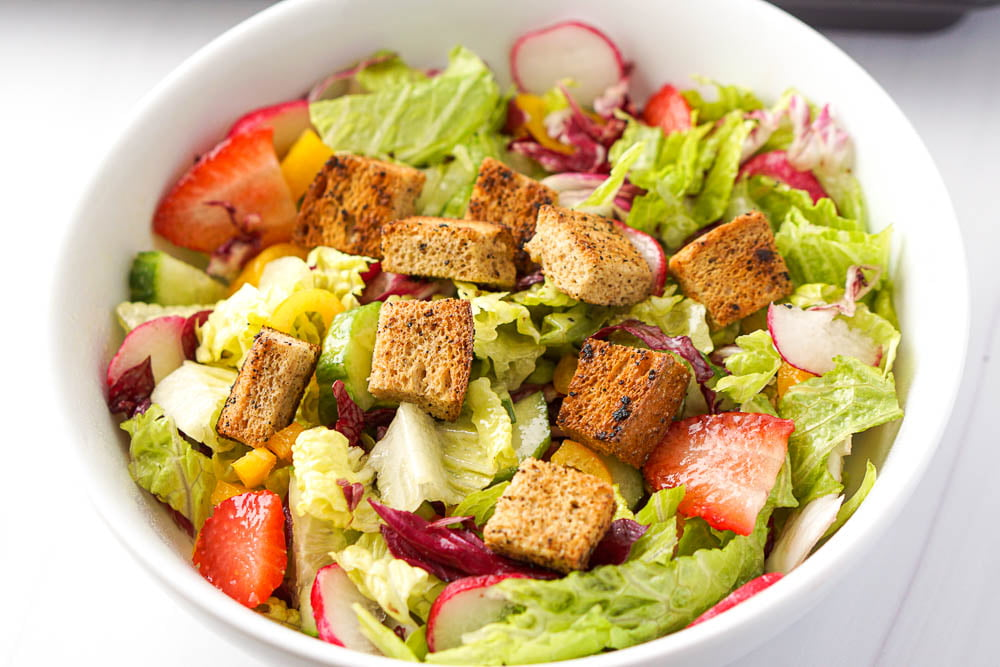 white salad bowl with low carb garlic croutons on top