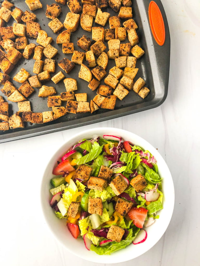 aerial view of a cookie sheet with garlic low carb croutons and a colorful salad with some on top