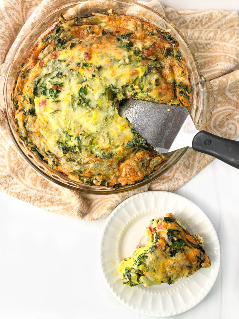 aerial view of a pie pan with low carb ham and spinach quiche with a white plate with a slice