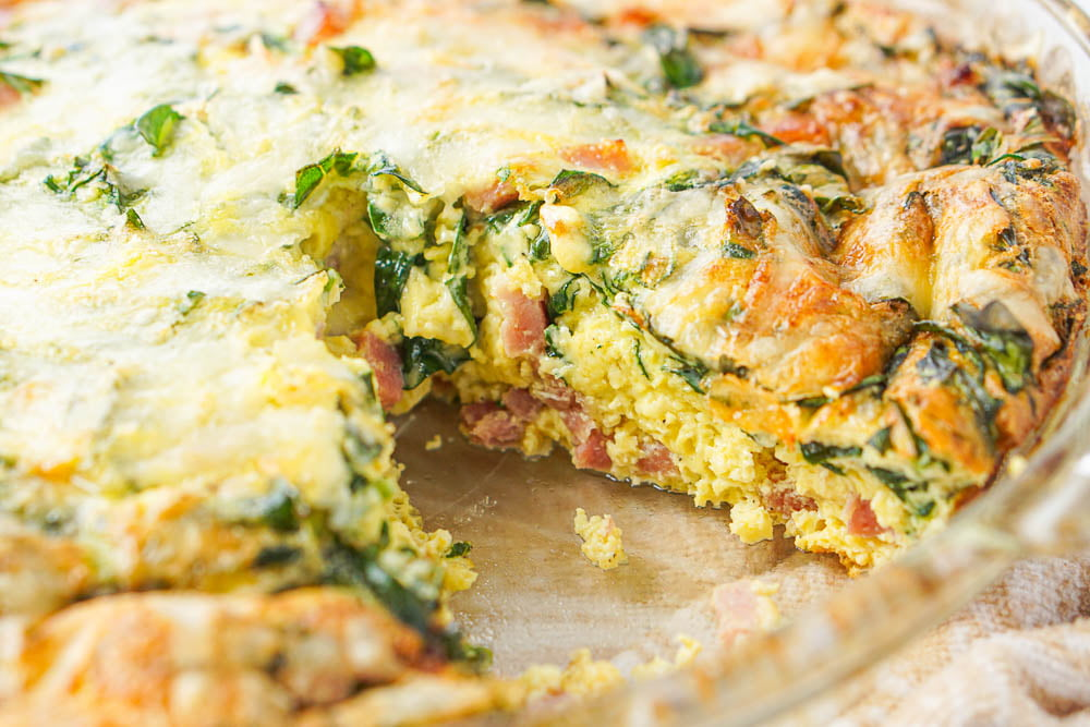 closeup of the pie plate with a slice of the keto quiche missing so you an see the fluffy eggs, ham and spinach