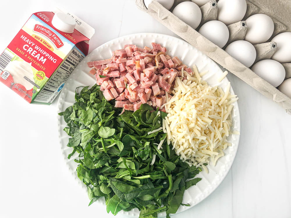 ingredients used in this recipe: carton of eggs, heavy whipping cream and a plate with chopped ham, spinach and shredded cheese