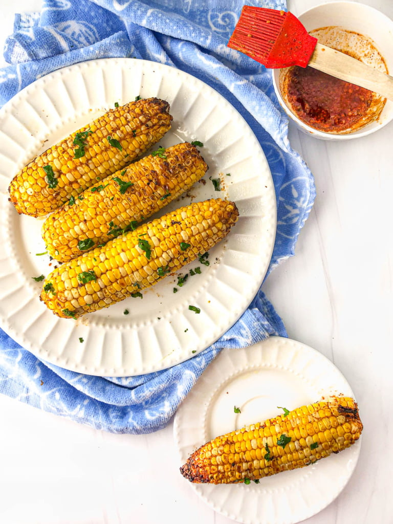 aerial view of a two with plates with Mexican corn on the cob and bowl of spicy butter