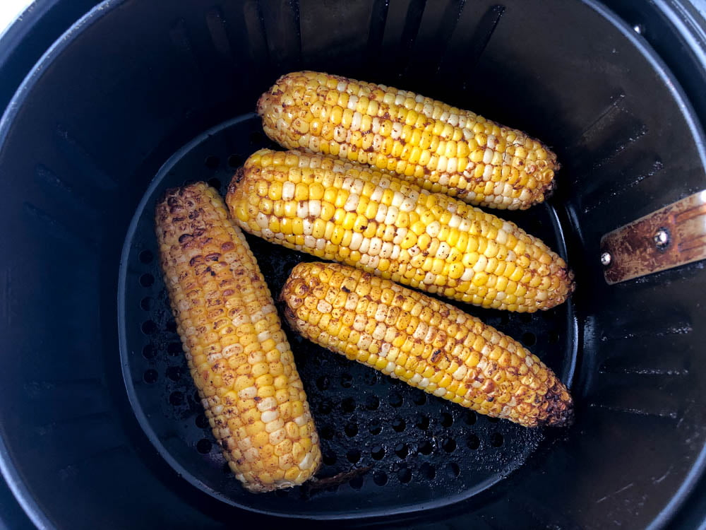 4 cooked ears of corn in the air fryer basket